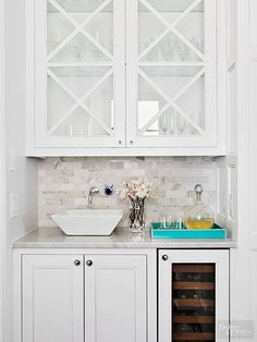 Switch up the look of a small wet bar with a contemporary vessel sink. This petite beverage station mixes modern and classic styles through the use of mullion cabinet doors and a square vessel sink./
