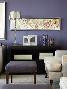 Love the painting against the purple grey wall colour and dark furniture.  The white chair reflects the white of the painting....as does the lamp shade.