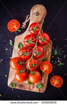 a bunch of fresh organic cherry tomatoes with sea salt and basil in olive cutting board by nblxer. a bunch of fresh organic cherry tomatoes with sea salt and basil on a dark background Knife Photography, Tomato Knife, Basil, Stock Photos, Vegetables, Image, Food, Essen, Vegetable Recipes