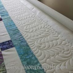 Free-Motion Quilted Feathers by Natalia Bonner of Piece N Quilt. Natalia teaches how-to quilt these in step-by-step photos in her book; Beginner's Guide to Free-Motion Quilting.