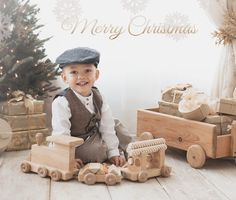 Beautiful Little Boy Playing with Toy Train for Christmas Mini Sessions