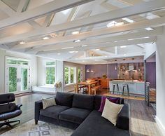 Midcentury Modern Renovation // Living Room and Kitchen + Open Floor Plan, Exposed Trusses + Eames Chair + Dark Stained Floor + Contemporary Windows + Painted Woodwork + Painted Trim