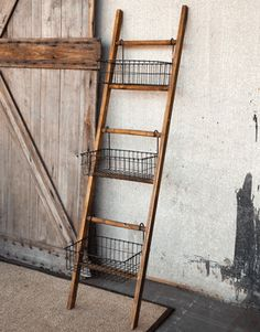 old ladder and wire baskets. I like that they are 'hung' from the upper wrung and resting on the lower rung