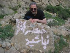 Iranian man posing behind Rock in taghbostan kermanshah mountain painted with slogan: khasteh nabshid which means: