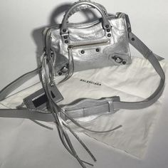 """Balenciaga Classic Mini City Cross-body -Classic Mini City-  •NWT•  -Description- •Mini version of iconic bag the """"City""""         •Silver lambskin leather w/ aged brass hardware           •hand braided top handles •2-way zip top closure w/ extended zipper & leather tassel pub tabs •Zip front pocket •1 internal zip pocket w/ Balenciaga embossed leather tag •Black fabric lining  •Detachable/adjustable leather shoulder strap  •Detachable leather mirror  •Made in Italy•  Balenciaga Bags Crossbody…"""