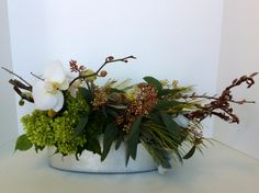 Long silver oval arrangement by McEwan Floral using cut white orchid stems, curly willow, green hydrangea, seeded eucalyptus, yellow craspedia and scabiosa pods