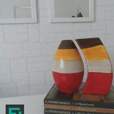 Detalhe decoração com vasos e papel de parede em  tijolo aparente branco, livros e espelho com moldura branca.