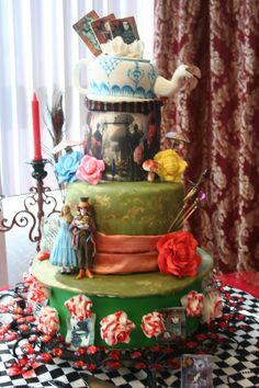Alice In Wonderland Wedding Cake - The cards and the cake with the scene are icing sheets with edible printing. The teapot is a cake and  the roses are all made fondant, the bottom layer of roses are painted with red gel colors.  The figures were supplied by the bride an are made of resin.The cake was made in separate layers and then transported 2 hours an assembled on location.
