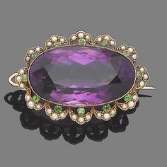 An amethyst, demantoid garnet and seed pearl brooch/pendant, circa 1900 The oval mixed-cut amethyst, within a fine millegrain-set border set with seed pearls and accented with circular-cut demantoid garnets, length Old Jewelry, Antique Jewelry, Vintage Jewelry, Purple Jewelry, Amethyst Jewelry, Suffragette Jewellery, Art Nouveau Jewelry, Pearl Brooch, Victorian Jewelry