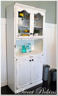 A wood hutch painted and distressed-glass busted out of the doors and replaced with spray painted chicken wire