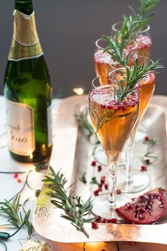 These Champagne Pomegranate Spritzers are a delicious, two ingredient cocktail garnished with rosemary sprigs. You'll enjoy the holiday cheer with these!