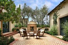 Patio. There are paved areas for outdoor living, usually made of tile, stone or brick. This courtyard patio has a Mediterranean influence and the floor is done in a herringbone pattern. Notice wrought-iron window grilles, a feature of Spanish architecture, in the fireplace wall.