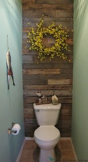 Tiny bathroom gets some personality with these wooden pallets for a backdrop.
