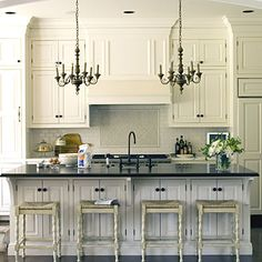 white cupboards+dark counter+chandeliers