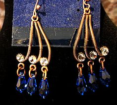 Copper wire dangle pierced earrings, approx 1.5 inches, clear Swarovski crystals embellish the setting and three blue sapphire dangle briolettes complete the design.  A very unusual setting and the co