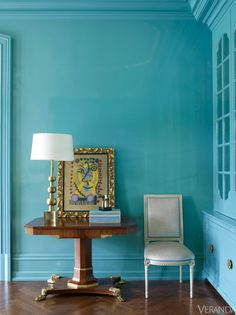 A vibrant turquoise defines this dining room, from the walls and upholstery to the fine trim on the chairs.