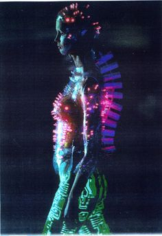 Tron inspired suit  with multicolour LEDs : Alexander McQueen at Givenchy , Paris .  Programmed flashing LEDs mounted on  transparent PetG body-hugging bodice , vac-formed from plaster body-cast. Concept by Alexander McQueen , designed and made by Studio van der Graaf , London. Two identical body suits were made , each with their own set of multicolour LEDs . Each model wears a 'stegosaur-style' 12 volt battery pack on her back . [tronlady.jpg]