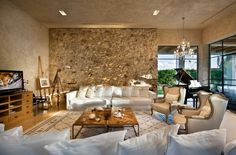 Villa: Wingback Chairs Also White Fabric Sofa Couch Mixed With Square Coffee Table Also Luxurious Rugs And Extruded Stone Walls On Deluxe Living Room Design Ideas: Exquisite Modern Villas Design