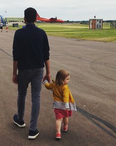 Day trip to the Imperial War Museum, Duxford.  A toddler is holding father's hand and walking towards the airplane