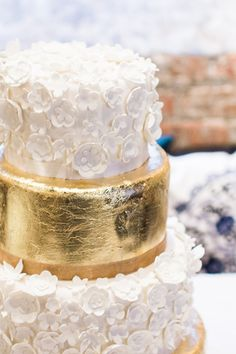 wedding cake with white flowers and gold foil