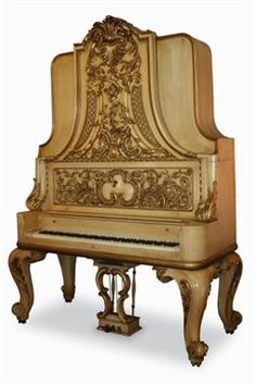 `Liberace` Piano An upright grand piano in an ornate cream and gilt case, together with a matching duet stool and twenty-four Liberace LPs. The Liberace book, 'The True Story,' by Bob Thomas, with a picture of the piano in his house is also included. Formerly the property of Liberace.