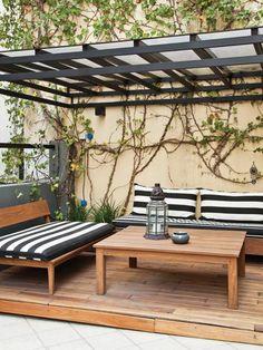 Terraza soñada en un departamento con pérgola de hierro pintada en negro, bancos y mesa de lapacho, deck de madera y enredadera.