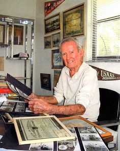 Former Navy Chief Tom Edwards looks at some of the pictures and plaques in his Deep Creek home chronicling his 22 year service career in the U.S. Navy. It began in 1940, just before the start of World War II. (Sun photo by Don Moore.)
