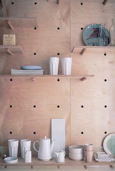 合板に孔を開けて有孔ボードの壁面収納にしてある壁
