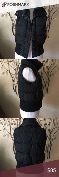 Theory black down vest This is a sized small black puffer vest from Theory.  Has a wide knit waist band and large knit collar.  Snaps and zipper.  Has front zip pockets.  Filling is grey duck down and feather. Purchased at Neiman Marcus. Measures 19 in across under arm hole with jacket snapped. Length is 20.5 in knit band at bottom is 4 in Theory Jackets & Coats Vests