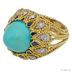 Sterle 18K gold cocktail ring with sapphire and diamond accents around a sugarloaf turquoise cabochon.  18K gold, turquoise, sapphires and diamonds.  France, c. 1960s.
