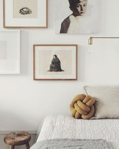 minimal bedroom with neutral palette and tonal gallery wall, knot cushion, brass sconce, wooden stool