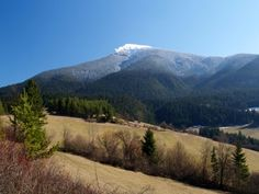 Fields above Vysny Kubin, Slovakia in spring. Peak of Choc mountain covered with snow can be seen in the distance.