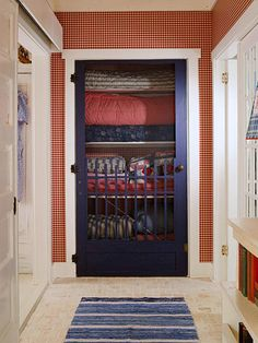 Unique Choice:   Red gingham wallpaper lines a hallway leading to a linen closet. A traditional screen door is a practical choice for homeowners who would like to both store and display lovely country quilts and linens.