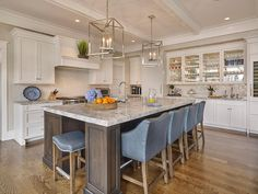 Chic kitchen features a pair of Osborne Lanterns illuminating a dark brown stained center island topped with gray quartzite countertops fitted with a stainless steel sink and high arc faucet lined with gray metallic slipcovered counter stools.