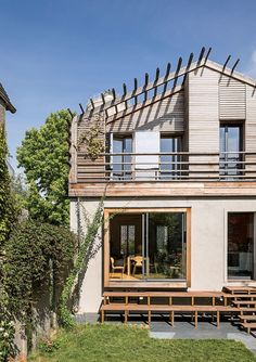 modern prefab home in Paris suburb with Technal sliding doors and windows, wood stairway to garden and concrete and red cedar facade