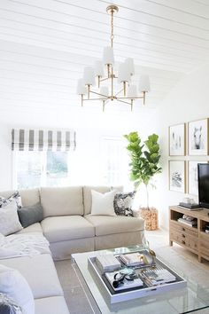 Family room in neutrals with slipcovered sectional, acrylic coffee table, and two-tiered chandelier