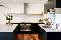 Matte black and timber accent kitchen. Sleek new contemporary kitchen with long timber shelf and feature wall shelf