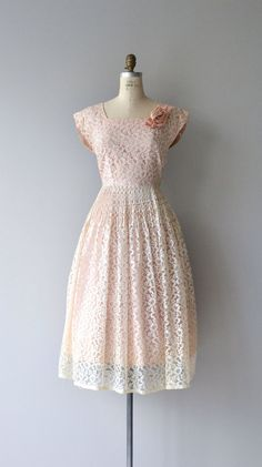 Vintage 1950s petal pink dress with white lace, square neckline, cap sleeves, pink rosette at one shoulder, fitted waist with some cartridge pleating.