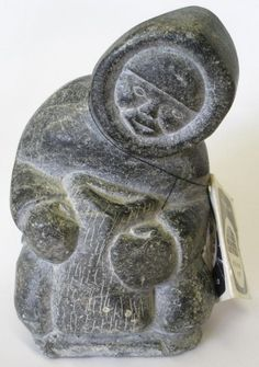 INUIT STONE CARVING OF A HOODED MAN CLUTCHING A BAG, SIGNED 779 WITH CANADA ESKIMO ART LABEL AND TAG, GREAT WHALE RIVER, NORTHERN QUEBEC, PURCHASED 1966
