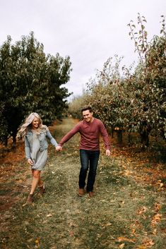 A couple walking through an orchard during their hood river oregon engagement