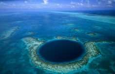 The Great Blue Hole by the livingmoon. Photo by David Doubilet: Located off the coast of Belize, the almost perfectly circular Great Blue Hole is a sinkhole which measures more than 300m across and 120m deep and is believed to have been formed as a limestone cave system during the last ice age when sea levels were much lower. As the ocean began to rise again the caves flooded, and the roof collapsed