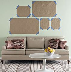 A tried and true picture hanging method. Cut scrap paper to the size of the frame and mark the nail location on the paper. Using painter's tape, move the paper templates around the wall until satisfied. Then hammer the nail through the marks.