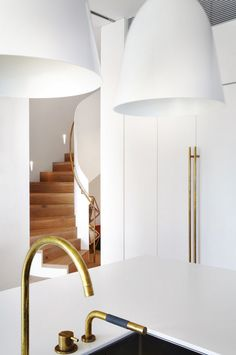 All white kitchen space with sleek gold detail + wooden stairway