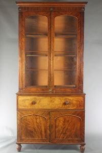 """Lot No 1286 A Victorian mahogany secretaire bookcase the upper section with moulded cornice, the interior fitted adjustable shelves enclosed by arched panelled doors above a well fitted secretaire drawer, the base fitted 6 short drawers enclosed by a pair of arched panelled doors, raised on turned supports 103""""h x 42""""w x 32""""d, sold for £480"""