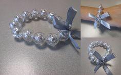 Pulseira elástica de pérolas transparentes com alumínio. Com laço de fita de seda. Tamanho: 18cm. Peça manufaturada.   Referência: OM003