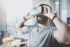 Bearded man wearing virtual reality goggles in modern coworking studio. Smartphone using with VR headset. Virtual Reality Goggles, Virtual Reality Games, Virtual Reality Headset, Vr Application, New Environment, Vr Headset, Change, Virtual World, Platform