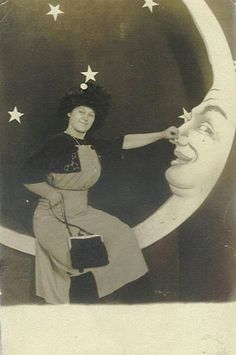 Vintage (c. WWI era) novelty arcade photo of woman leaning on the nose of a paper moon