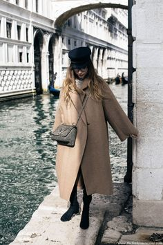 Fashion blogger Beatrice Gutu in Venice wearing HM Trend oversized camel coat with Louis Vuitton twist bag and suede over the knee boots
