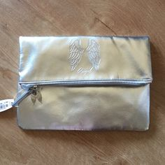 """VS silver foldover clutch Angel NWT A beautiful silver metallic clutch with a simple zip closure and a fold over detail. Lining is pink and red stripes. Has angel wings embossing with the word """"Angel"""". Also has angel wings pendant on zipper. Not sure what the material is but likely pebbled faux leather. Has two tiny dents in front as seen in second pic. Has two dent lines in back right under the angel sign as shown in last pic. Unfolded height is 11.5 inches. Folded height is 7.5 inches…"""