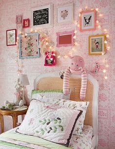 O fio de lâmpadas destaca a decoração do quarto de Manuela, 3 anos. Ele fica sobre os quadrinhos dispostos de forma irregular. Projeto da arquiteta Monica Drucker